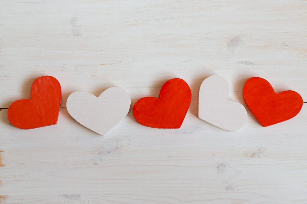 Red and white hearts on white wooden background
