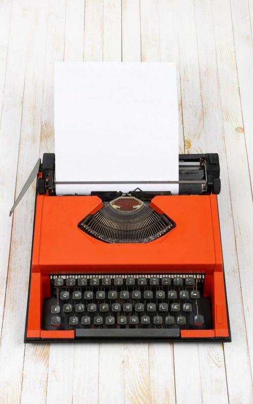 red-typewriter-on-white-wood-plank (1) (1)